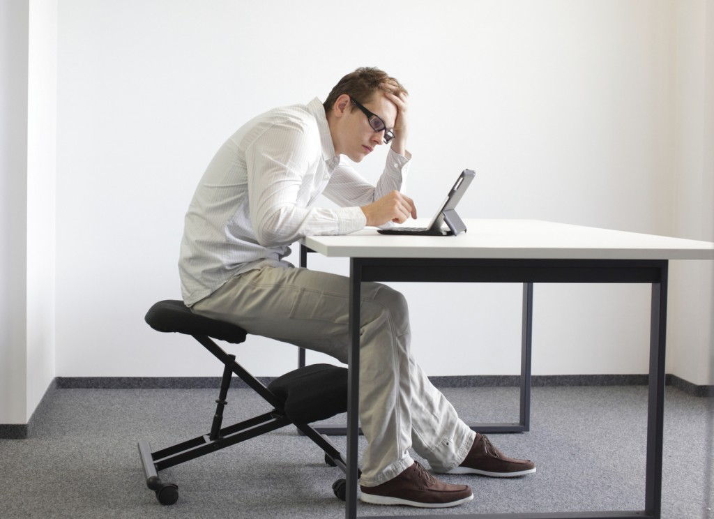 man is bent over  tablet.Bad sitting posture at work