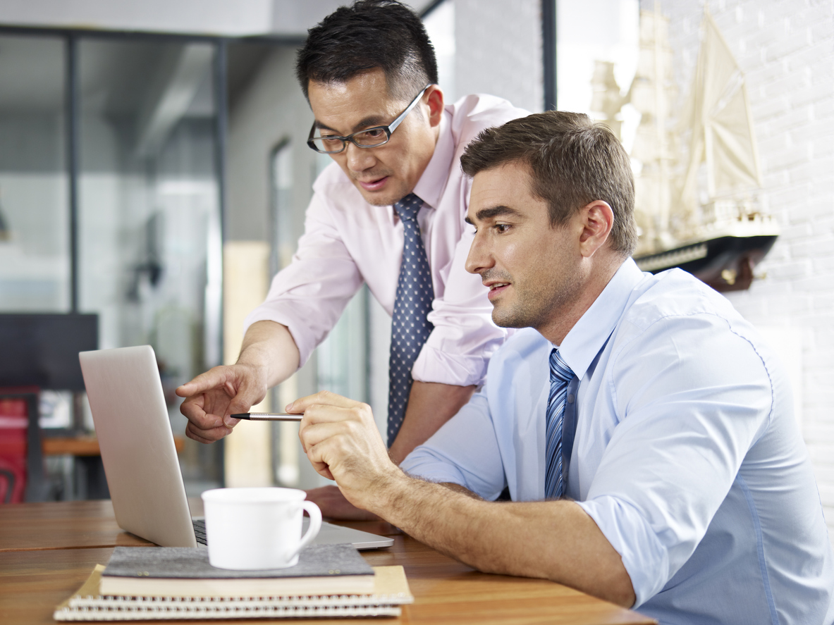 asian and caucasian businessmen working together in office