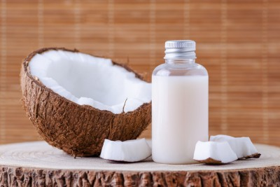 cosmetic bottle and fresh organic coconut for skincare, natural background