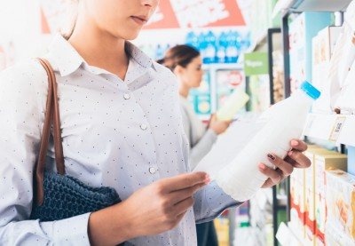 Woman shopping at the supermarket, she is holding a milk bottle and reading her shopping list