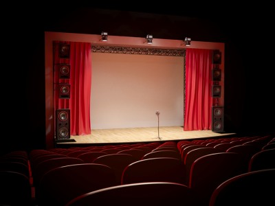 Concert hall with a red curtain and a microphone on the counter.