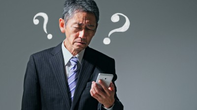Senior asian businessman looking at a smart phone. Presbyopia concept.