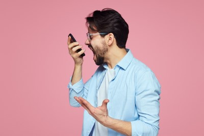 Portrait of a furious young businessman yelling at mobile phone isolated over pink background.