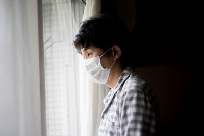 A sick Japanese man wearing a surgical mask is standing by the window